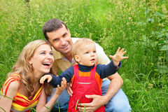 Parents with child sit in grass Stock Photography