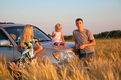 Parents and child sitting on car cowl on wheaten f Royalty Free Stock Images