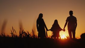 Parents with the child stand in a picturesque place, admiring the sunrise. Holding hands. Happy family concept