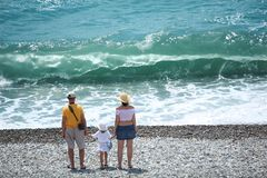 Parents with child stand on seacoast,  rear view Stock Photos