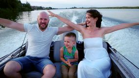 Parents with a child on a summer outing on the river, happy family in a boat, Mom and Dad spend time with his son having stock video