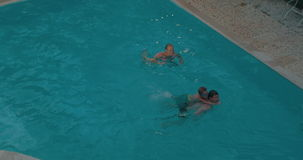 Parents and child swimming in the pool stock footage