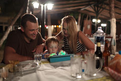 Parents and child with tablet PC in outdoor cafe Royalty Free Stock Image