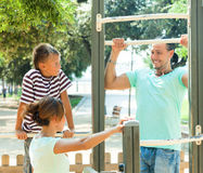 Parents with child  training with pull-up bar Royalty Free Stock Image