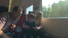 Parents and child traveling by train and using cellphone. Mother, father and son traveling by express train in the city. Mom and child playing with smart phone stock footage