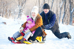 Parents with child walking in a winter park. Family walking in a winter park. Parents with child on sled Stock Photography