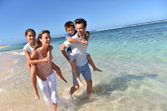 Parents with children on the back walking in the sea. Parents giving piggyback ride to kids on a sandy beach Stock Photography