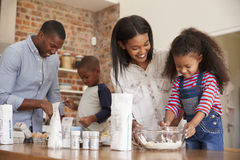 Parents And Children Baking Cakes In Kitchen Together Stock Image