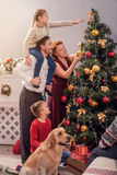 Parents and children beautifying fir-tree. Happy family is decorating Christmas tree together. Father is holding daughter on shoulders and smiling. Boy is Stock Image