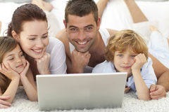 Parents and children in bed using a laptop Stock Photo