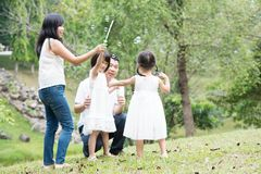 Asian family blowing soap bubbles at park. Parents and children blowing soap bubbles at garden park. Asian family outdoors activity royalty free stock photography
