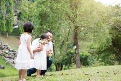Happy Asian family blowing soap bubbles at park. Parents and children blowing soap bubbles at garden park. Asian family outdoors activity royalty free stock photos