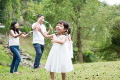 Asian family blowing soap bubbles outdoors. Parents and children blowing soap bubbles at park. Asian family outdoors activity royalty free stock photo