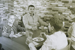 Parents and children chatting during dinner in family cafe. Parents and children chatting during dinner in comfortable family cafe Stock Photo