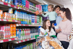 Parents with children choosing dairy products Stock Photo