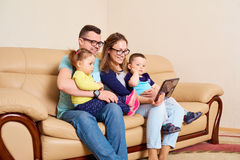 Parents and children click on the tablet in the room.  royalty free stock photography