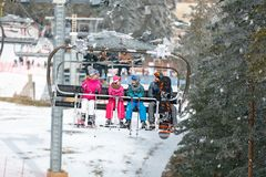 Parents with children climb up on the ski terrain with chair lift royalty free stock images