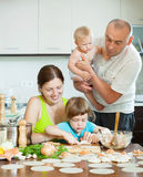 Parents with children dumplings fish cooking in a home kitchen Stock Images