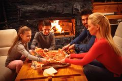 Parents and children eating pizza together Royalty Free Stock Photography