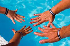 Family hands with all inclusive bracelets by resort swimming pool. Parents and children enjoying summer vacation in hotel. Holidays, travel destination, fun royalty free stock images