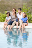 Parents with children enjoying by the swimming pool Stock Photography