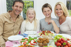 Parents Children Family Healthy Eating Salad Table. An attractive happy, smiling family of mother, father, son and daughter eating healthy salad at a dining stock photography
