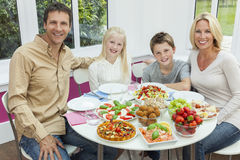 Parents Children Family Healthy Eating Salad Table. An attractive happy, smiling family of mother, father, son and daughter eating healthy salad at a dining stock photo