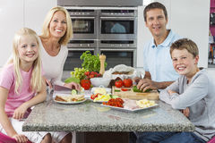 Parents Children Family Preparing Healthy Food. An attractive happy, smiling family of mother, father, son and daughter preparing and eating healthy food in royalty free stock photography