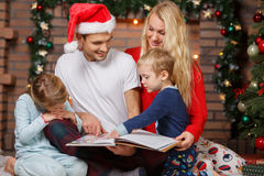 Parents with children by fireplace royalty free stock photography