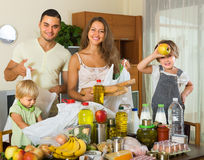 Parents and children with food. Happy family with little children sorting purchased food out indoor royalty free stock images