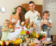 Parents and children with food. Happy parents with female children sorting purchased food out indoor Stock Image