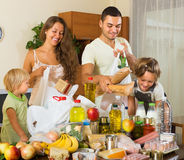 Parents and children with food. Happy smiling parents with female children sorting purchased food out indoor royalty free stock photography