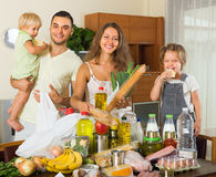 Parents and children with food. Positive family with little children sorting purchased food out indoor Royalty Free Stock Photo