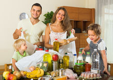 Parents and children with food. Smiling family with little children sorting purchased food out indoor. Focus on woman Stock Image
