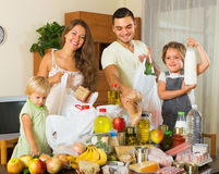Parents and children with food. Smiling parents with female children sorting purchased food out indoor Stock Photography