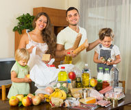 Parents and children with food. Smiling young parents with female children sorting purchased food out indoor stock photos