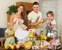 Parents and children with food. Young parents with female children sorting purchased food out indoor Stock Photos