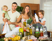 Parents and children with food. Young smiling family with little children sorting purchased food out indoor Royalty Free Stock Photo