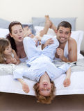 Parents and children having fun in bed Stock Photo