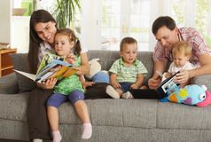 Parents and children having fun at home. Happy nuclear family with three children having fun sitting on sofa at home, reading books, smiling stock photos