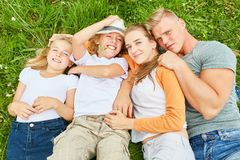Parents and children lie relaxed in the grass stock photo