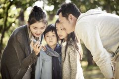 Parents and children looking at cellphone together royalty free stock photo