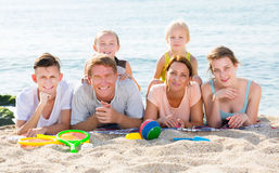Parents with children lying on sand Stock Photo