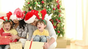 Parents and children opening Christmas gifts at home stock video