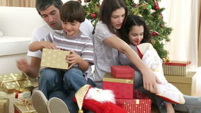 Parents and children opening Christmas presents Stock Image