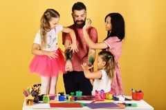 Parents and children paint on fathers arms with gouache. Family leisure time and art concept. Girls, men and women with happy faces by art desk on yellow royalty free stock image