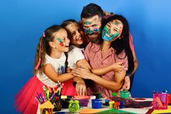 Parents and children painted with gouache. Family leisure time. And art concept. Artistic family hugs on blue background. Girls, men and women with happy stock photography