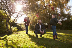 Parents And Children Playing With Autumn Leaves in Garden Stock Photography