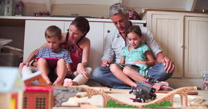 Parents And Children Playing With Digital Tablets In Bedroom. Parents and children playing with digital tablets - traditional wooden toys in foreground.Shot in stock video footage