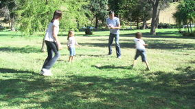 Parents and children playing in a park with a ball. Footage in high definition of parents and children playing in a park with a ball stock footage